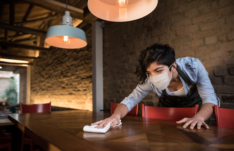 Waitress At A Restaurant Wearing A Facemask And Cleaning The Tables
