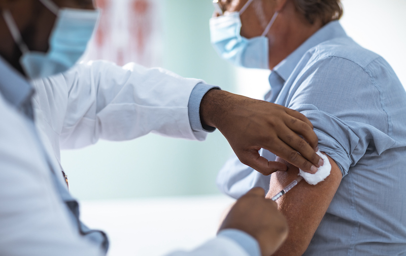 Mature Man Taking A Vaccine From His Doctor