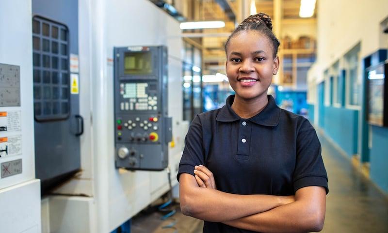 Woman Technician Standing In Factory Shop Floor