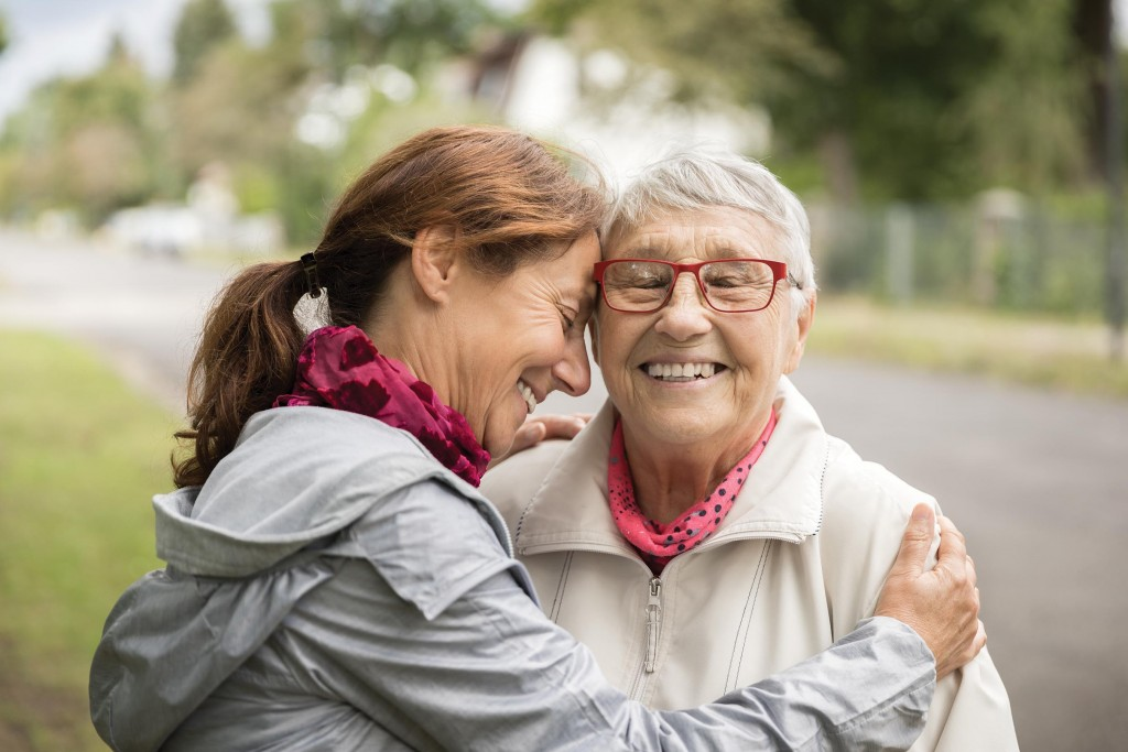 Happy Senior Woman And Caregiver Walking Outdoors