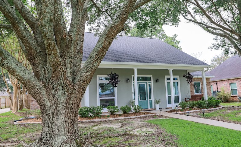 A Front View Of An Acadian Renovated Home With Columns, Sidewalks And A Colorful Front Door Recently Purchased With The Changing Real Estate Market