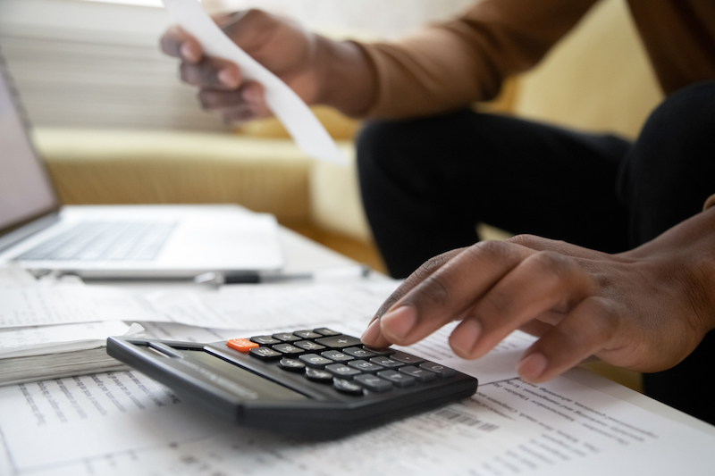 Close Up Of African American Man With Calculator Checking Bills