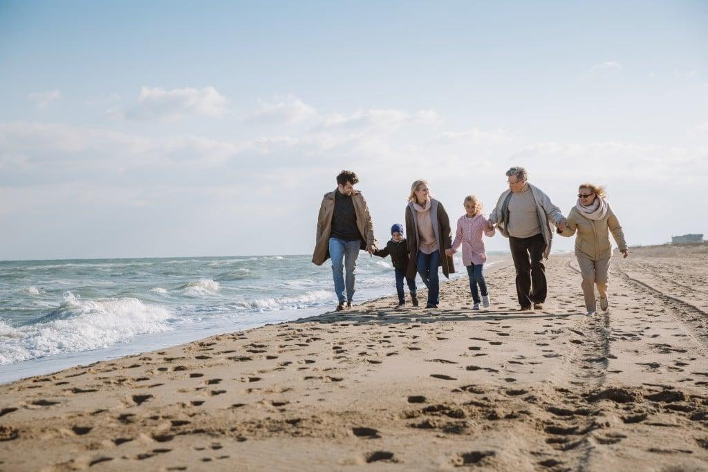 Big,multigenerational,family,walking,together,on,beach,at,seaside