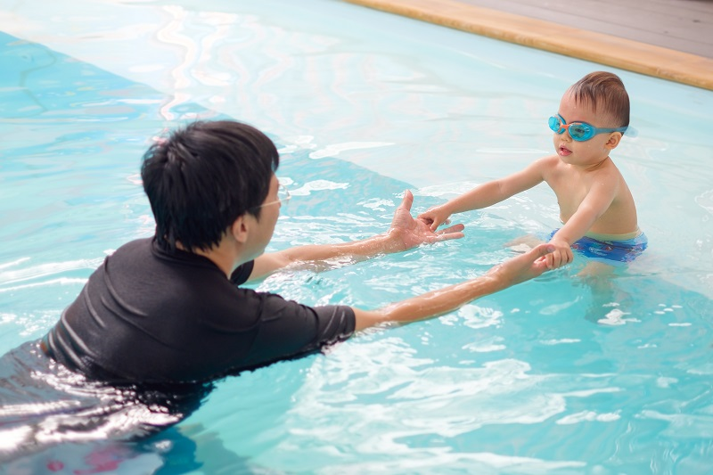 Asian Father & Happy Cute Little Asian 24 Months Toddler Boy Child In Trunks Wear Swimming Goggles Relaxing Playing In Indoor Swimming Pool