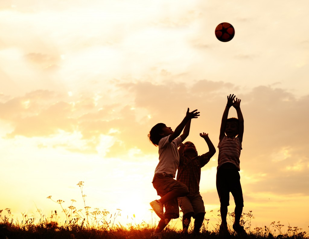 Group,of,happy,children,playing,with,ball,on,meadow,,sunset,