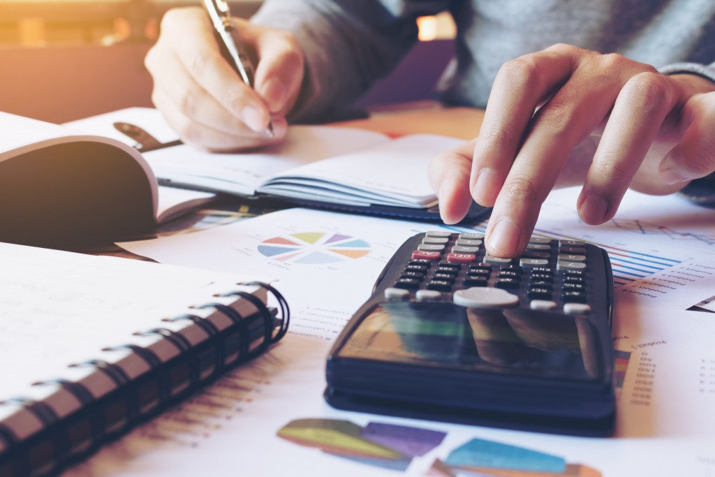 Hand,man,doing,finances,and,calculate,on,desk,about,cost