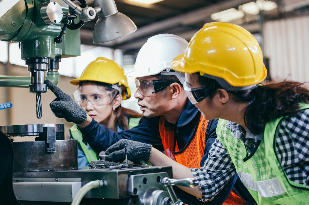 Asian,male,foreman,manager,showing,case,study,of,factory,machine