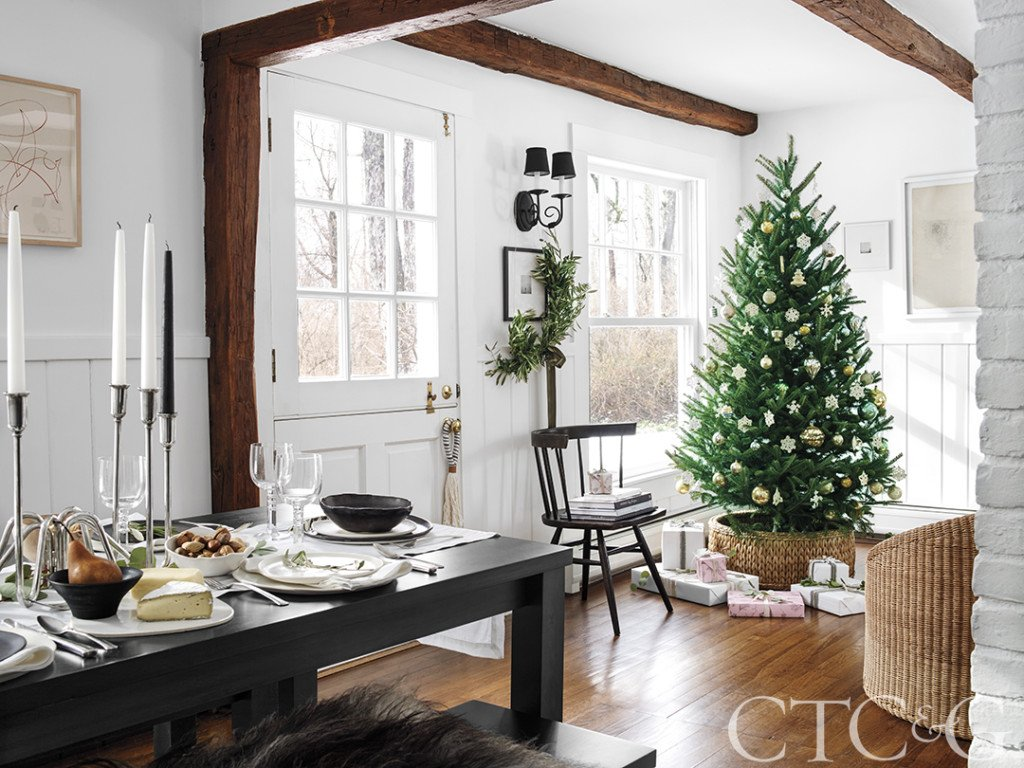 Country house interior with Christmas tree, black dining table, woven tree stand, antique beams