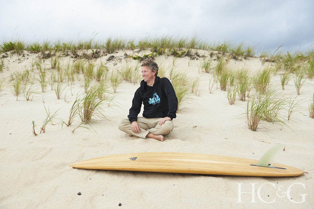 Man sitting cross legged in the sand in front of wooden surfboard.