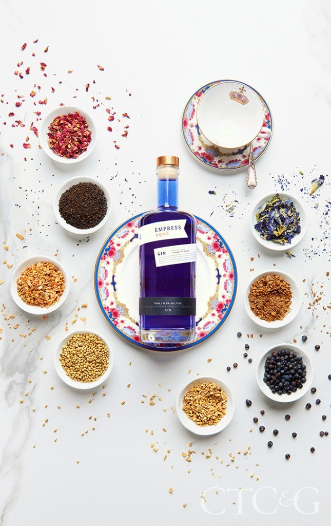 A royal blue gin bottle on a pink and blue plate.