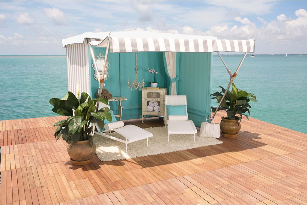 A wooden dock with a seaside pavilion, featuring a white striped canopy, white lounge chairs, a white carpet, and large potted plants.