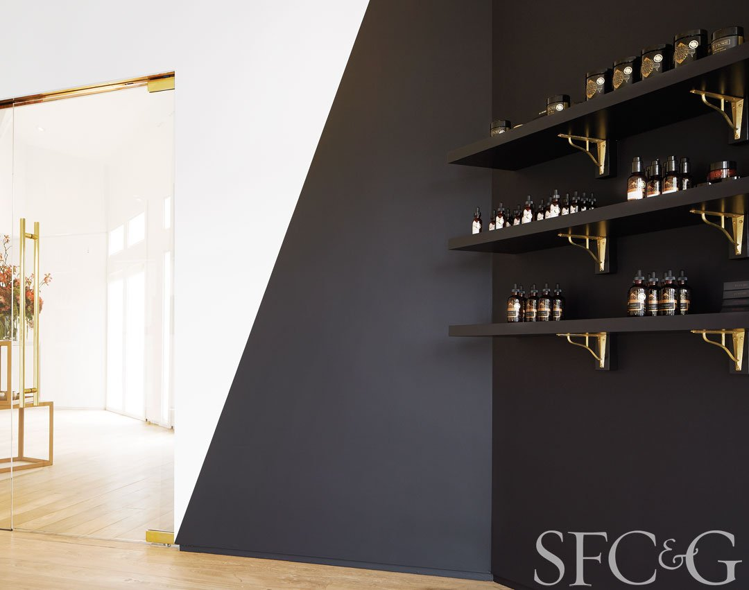Lacquered brass finishes glow against a graphic black accent wall.