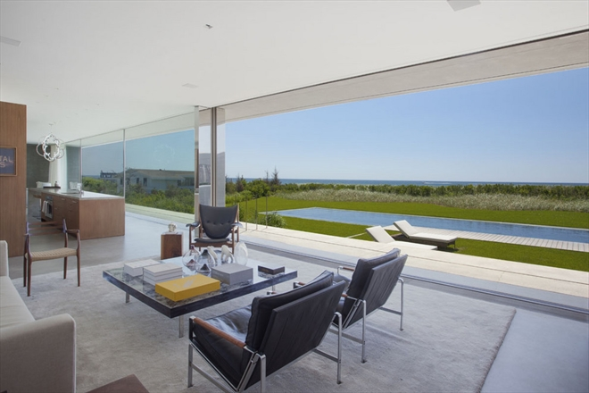 A glass wall in the living room has a view of the pool.