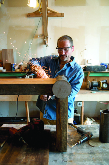 In his Wainscott workshop, Kevin Damm of Re-Livefurniture fabricates a table made from reclaimed wood and steel tubing