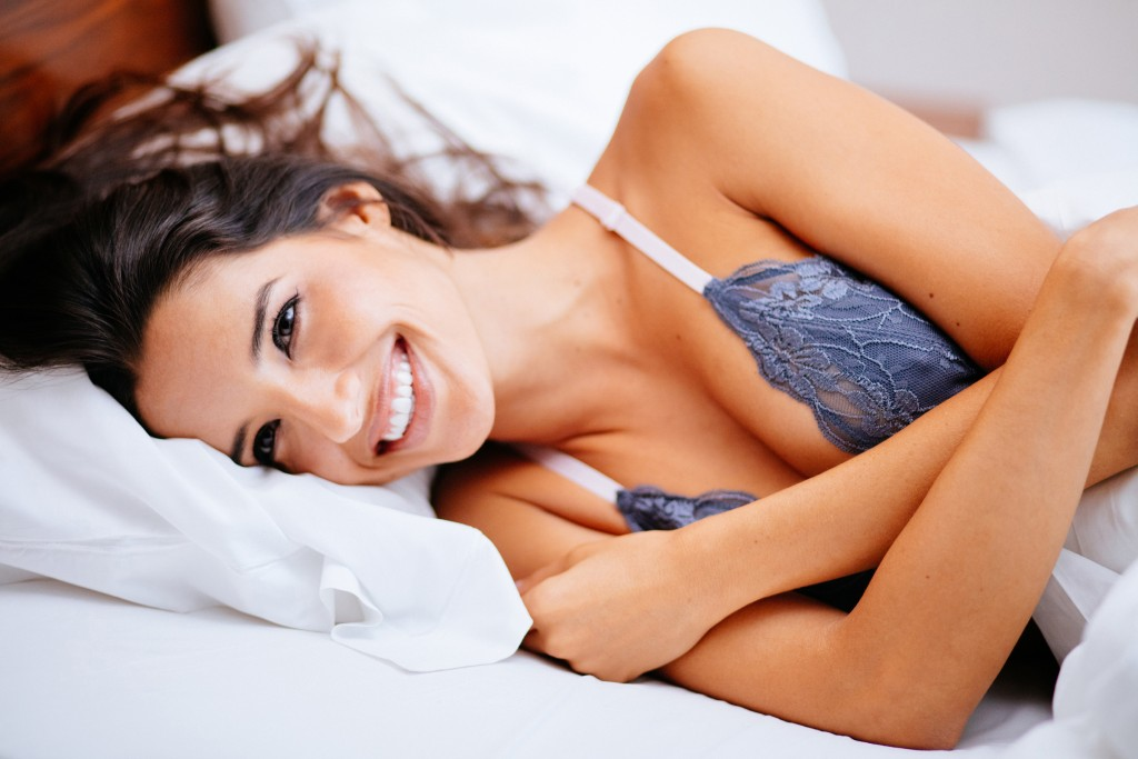 Women With Big Toothy Smile Is Lying In Bed