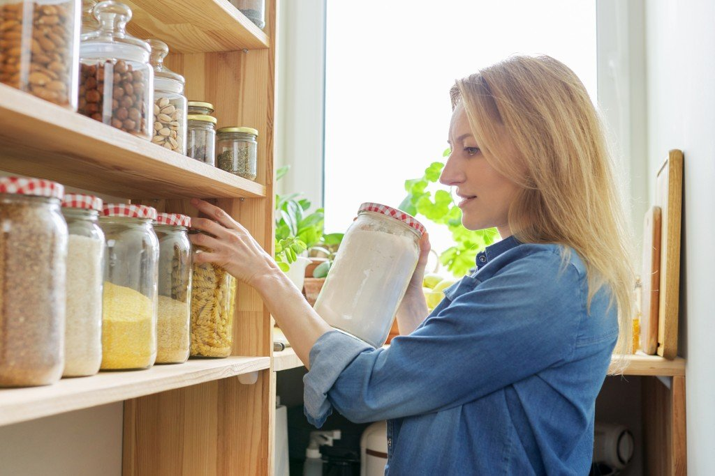 Middle Aged Woman At Home In Kitchen In Pantry