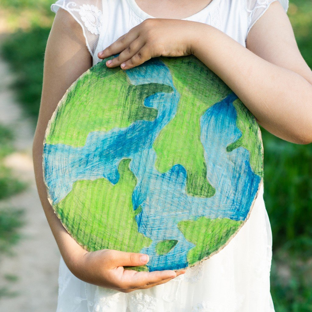 Protection And Love Of Earth. Little Girl Holding Planet In Hands Against Green Spring Background. Earth Day Holiday Concept.