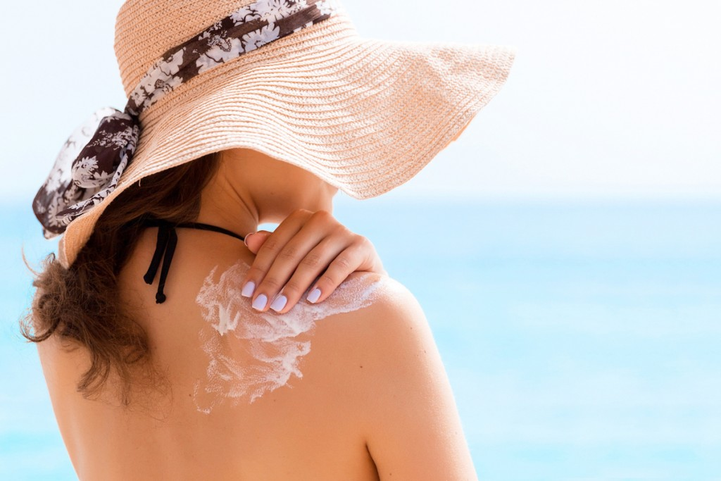 Beautiful Woman In Hat Is Putting Sun Cream On Her Shoulder At The Beach