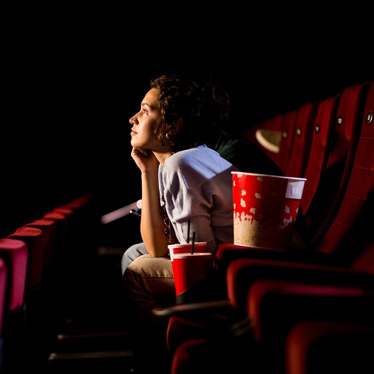 Young Woman Enjoying Watching Movie At The Cinema