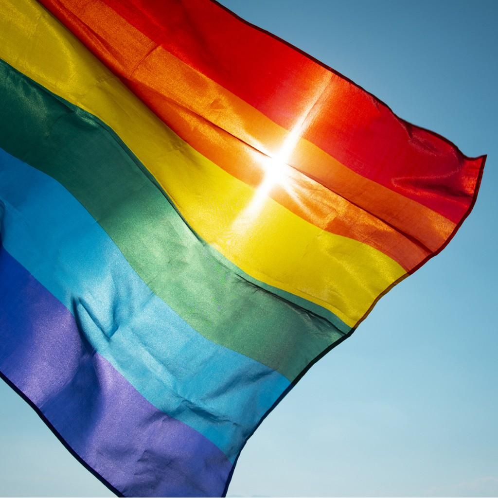 Rainbow Flag Waving On The Blue Sky