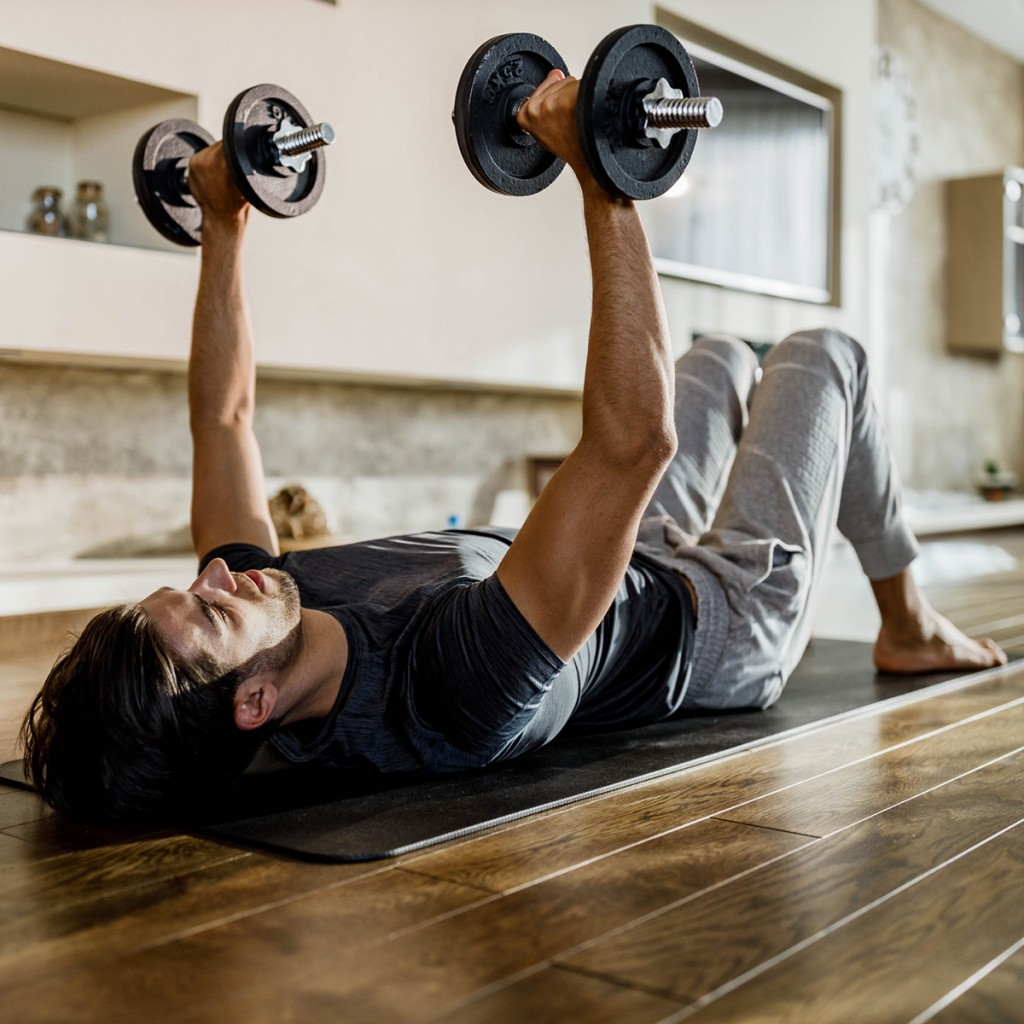 Muscular Build Man Exercising Strength With Weights On A Floor.