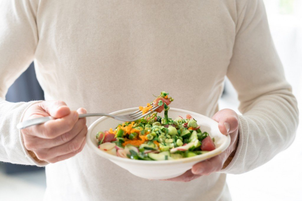 Healthy Man At Home Eating A Salad