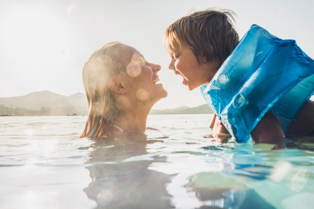 Happy Mother And Son Having Fun While Swimming In Sea On Summer Vacation.