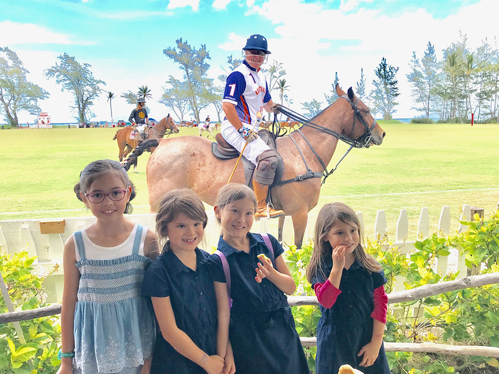 Kids smiling in front of ponies at Hawaiʻi Polo Club