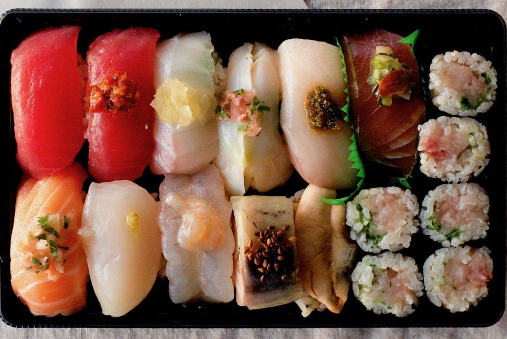 takeout box of luxe nigiri sushi topped with jewel-like garnishes