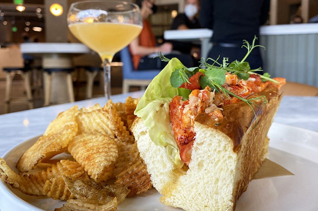 elegant lobster roll plated with chips and cocktail in background