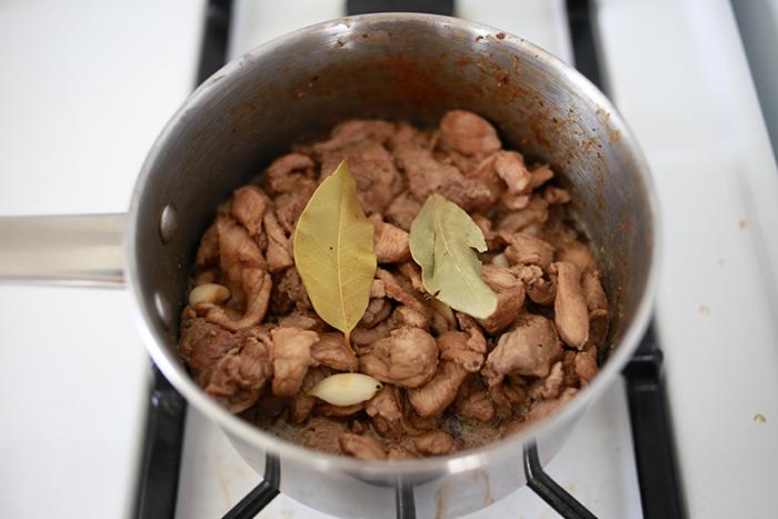 After the pork is brown turn down the heat. Add 1/2 cup of water and 2 bay leaves. Let the meat simmer for 45 minutes to 1 hour. Serve hot and enjoy.