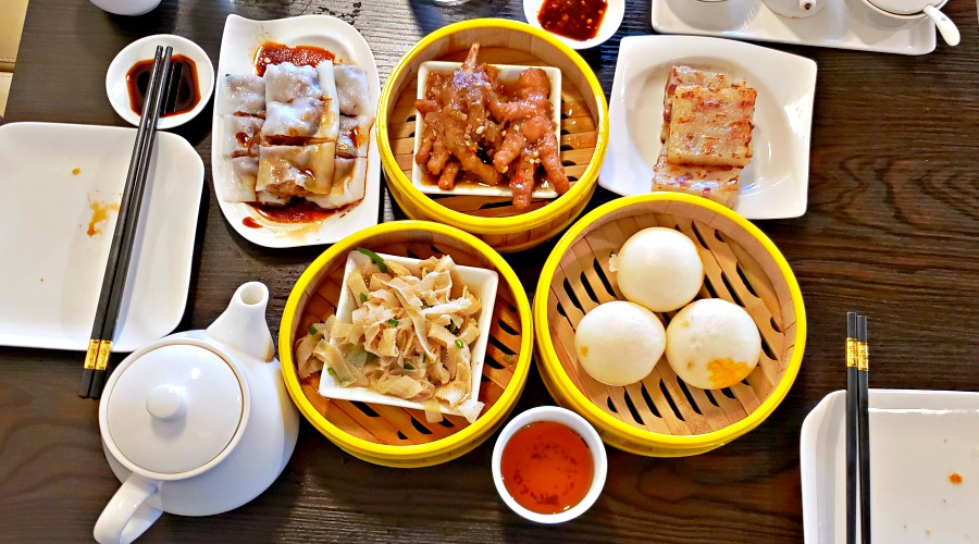 array of plates holding a multitude of dim sum is spread across a tabletop