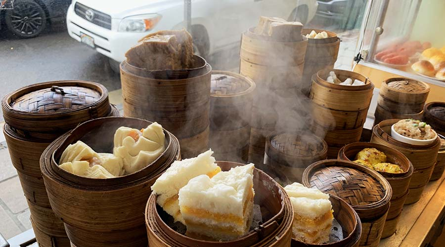 stacks of steamers hold plump morsels of dim sum in a shop window