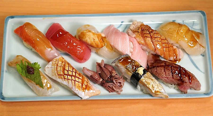 assortment of high-end nigiri sushi glisten on a wooden sushi tray
