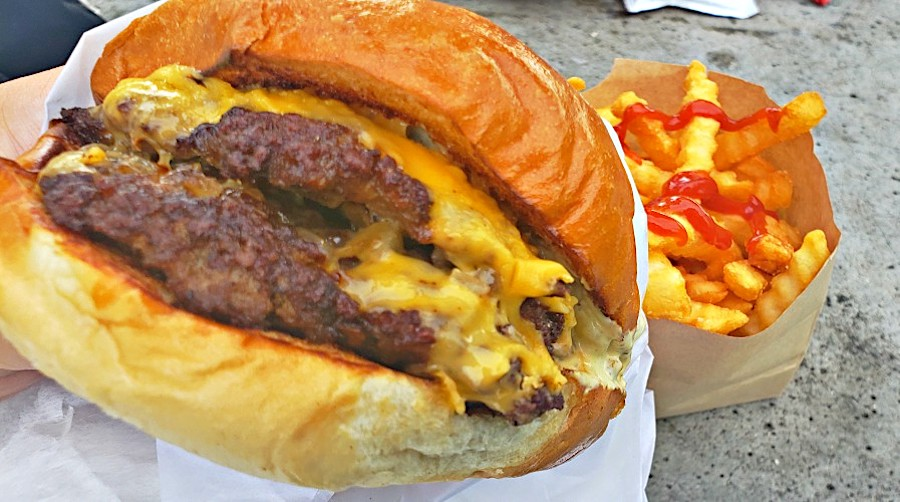 close-up of cheesy smash burger with fries and ketchup in background