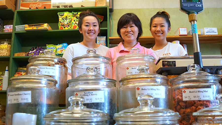 members of the fang family smile behind a row of crack seed jars