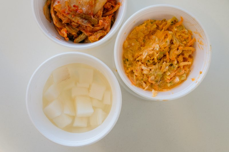 I'm confused about the sides or panchan, because unlike every other Korean restaurant I've been to, you have to order and pay for them. Clockwise from top: kimchi ($3.25), kimchi coleslaw ($3.25), pickled radish ($2.25).