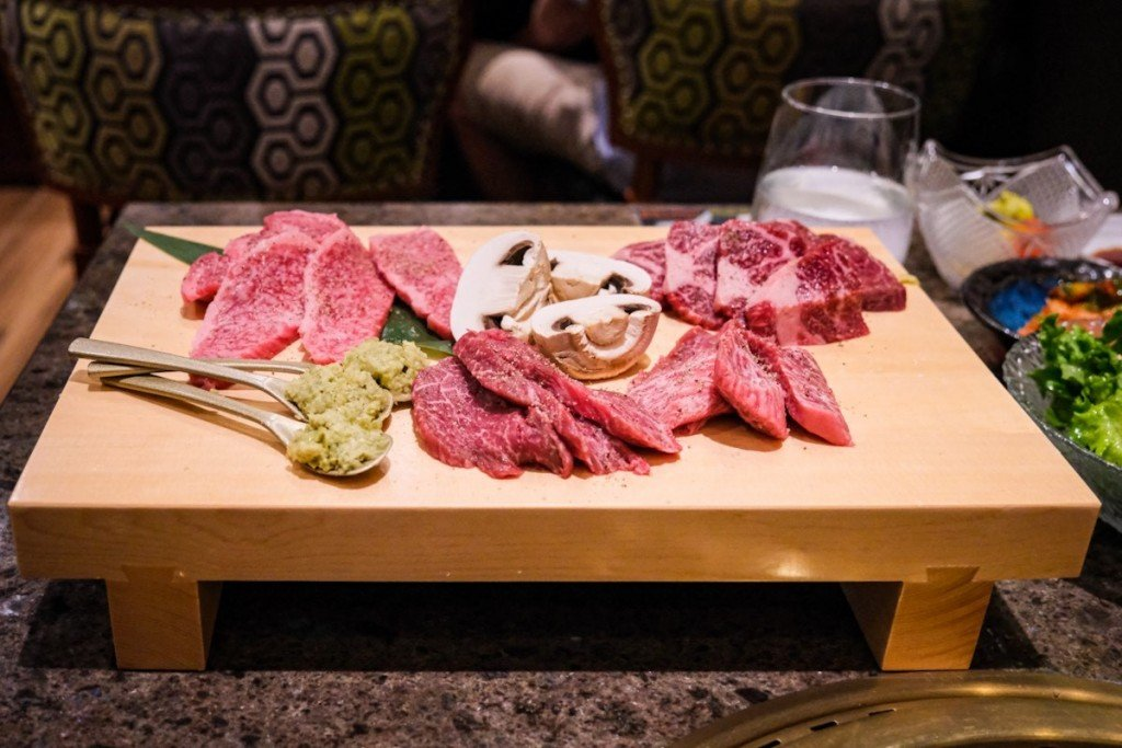 cuts of well-marbled a5 wagyu and king mushrooms await the grill on a pristine wooden geta at tableside