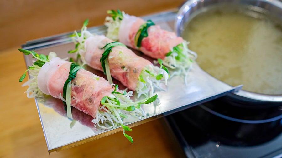 pork belly rolls next to hot pot