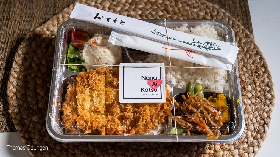 neatly wrapped bento with crispy tonkatsu, rice and side dishes