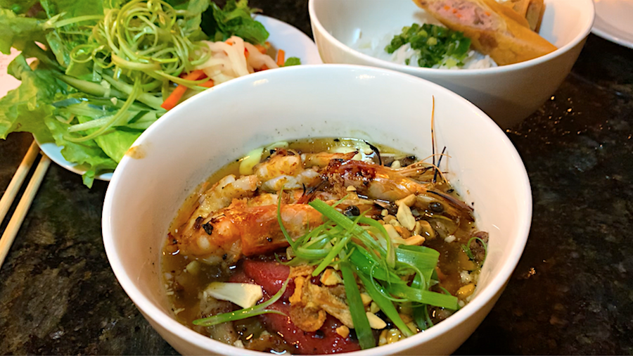 vibrant bowls of grilled pork and shrimp, rice vermicelli noodles and fresh herbs waiting to be mixed together