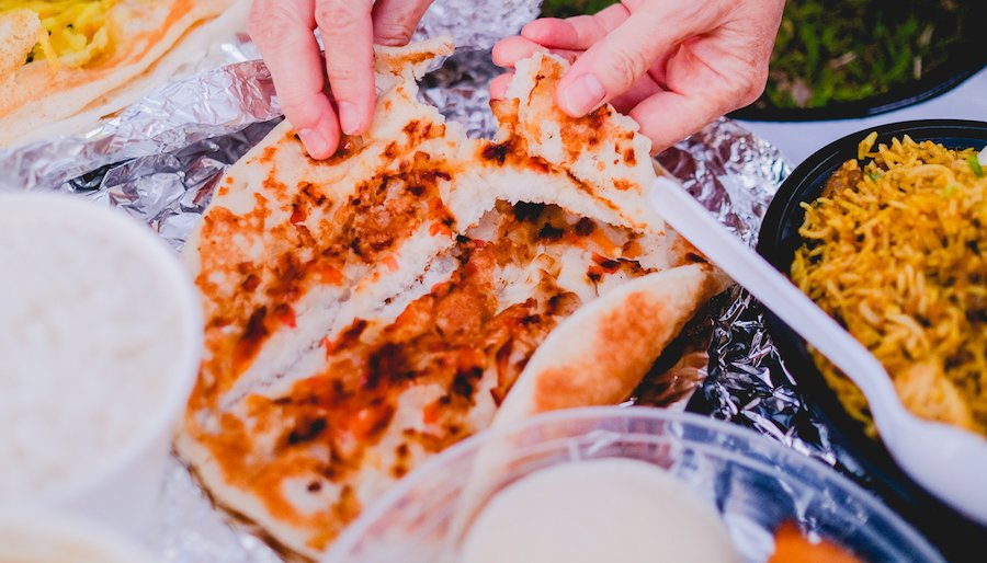 hands tear a large round of indian dosa-style flatbread