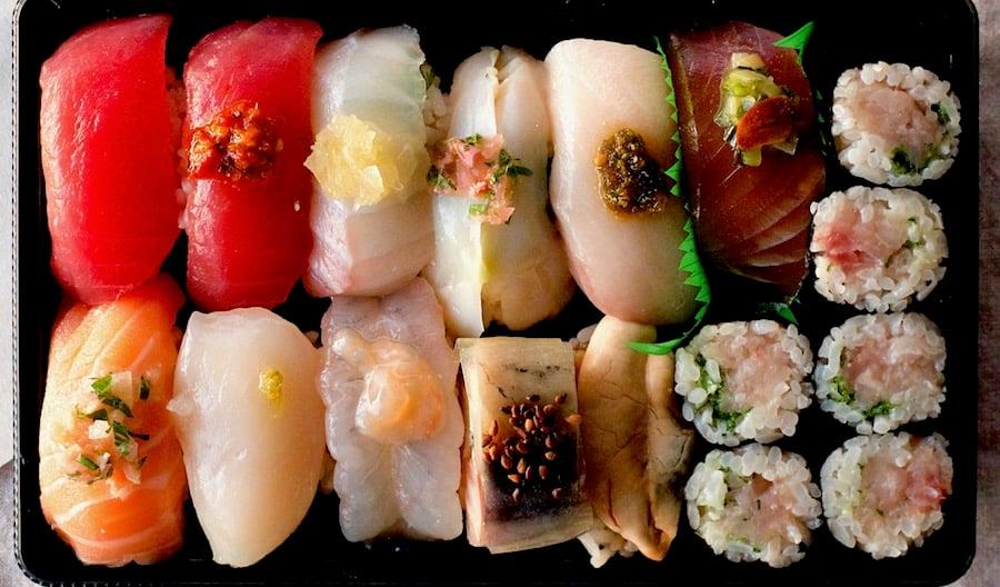 high-end omakase sushi in a takeout box glisten like jewels of nigiri