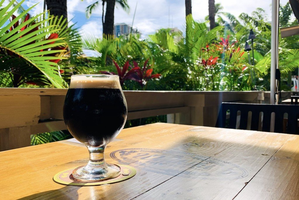 goblet of dark porter sits on a wooden table in front of sunlit tropical foliage