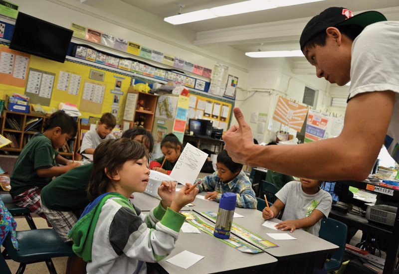 Pacific Buddhist Academy senior Andrew Tom assists  students during his internship at Palolo Elementary School.