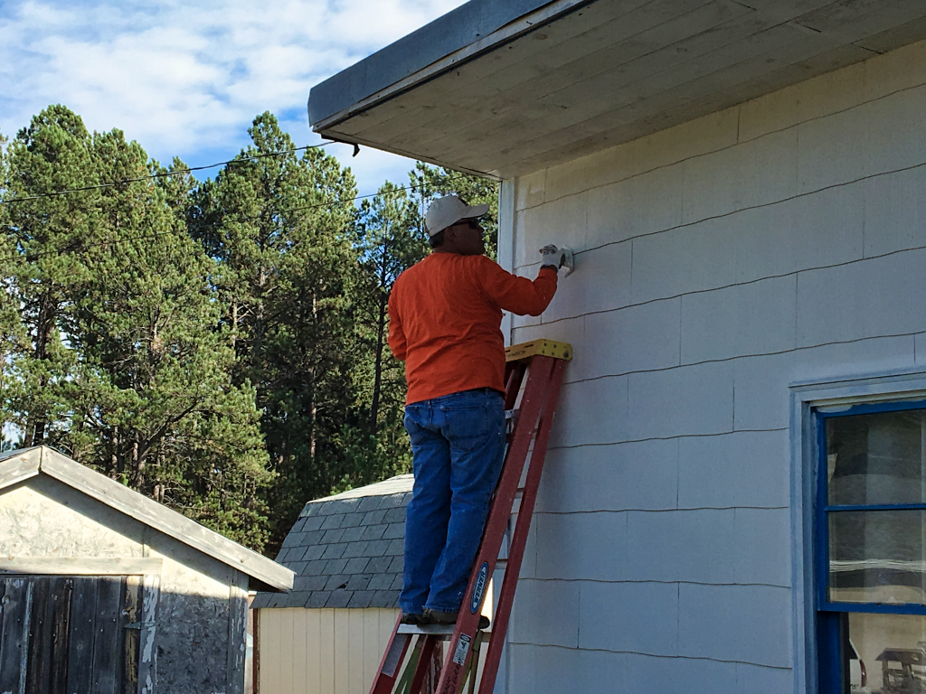 A volunteer applies primer to the home of Pat Spargur in Custer. The home was built in 1947, has original windows, and has not been painted in decades. Volunteers organized by the Black Hills Home Owners Association's Builder Care Project is performing the work. Photo Date: Sep. 22, 2018.
