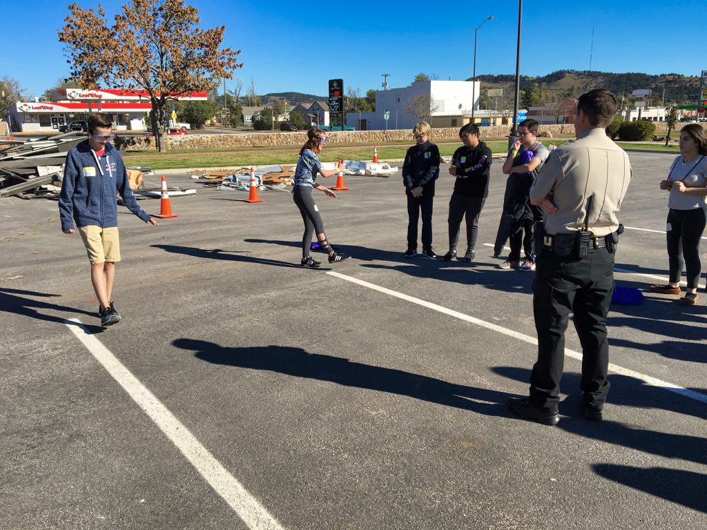 Two freshmen take a field sobriety test wearing goggles that simulate a BAC of 0.25, or roughly 3 times the legal limit. The exercise was part of the annual Freshman Impact event, which brings teens face-to-face with the consequences of risky decisions regarding alcohol, drugs, and suicide. Photo Date: Oct. 17, 2018.