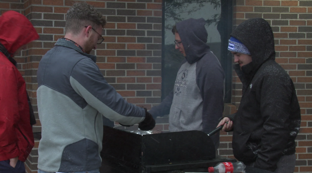 SDSMT students grill outside during a snowstorm for their annual 'Night in the Cold' event which educates the public about homelessness.