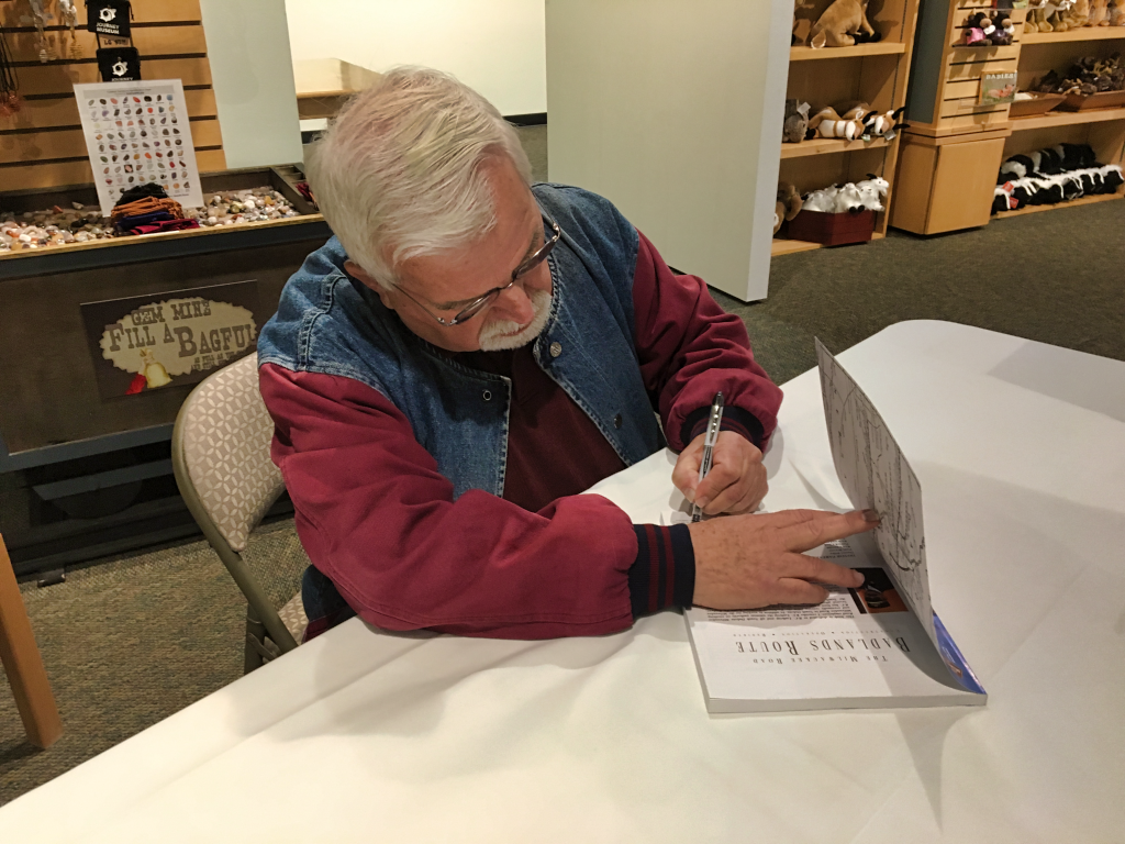 """Author Gary Holzinger signs a copy of """"The Badlands Route"""" at the official presentation of the book at the Journey Museum in Rapid City Sunday. Photo Date: Nov. 4, 2018."""