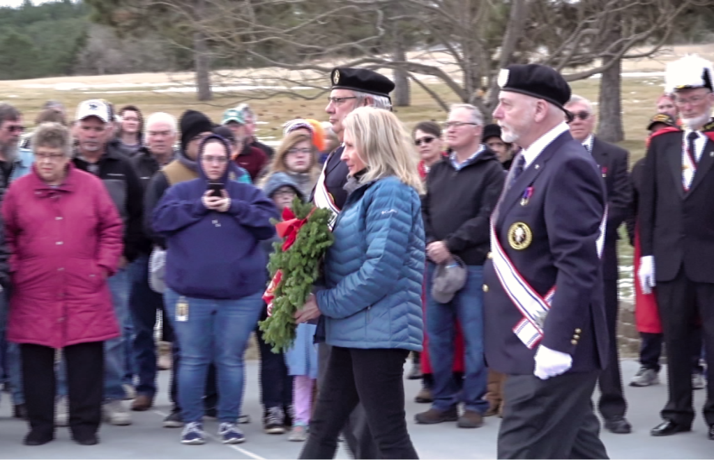 A family member of a deceased veteran, flanked by members of the Knights of Columbus, prepares to lay a wreath to honor deceased and missing veterans Saturday at Black Hills National Cemetery. Photo Date: Dec. 15, 2018.